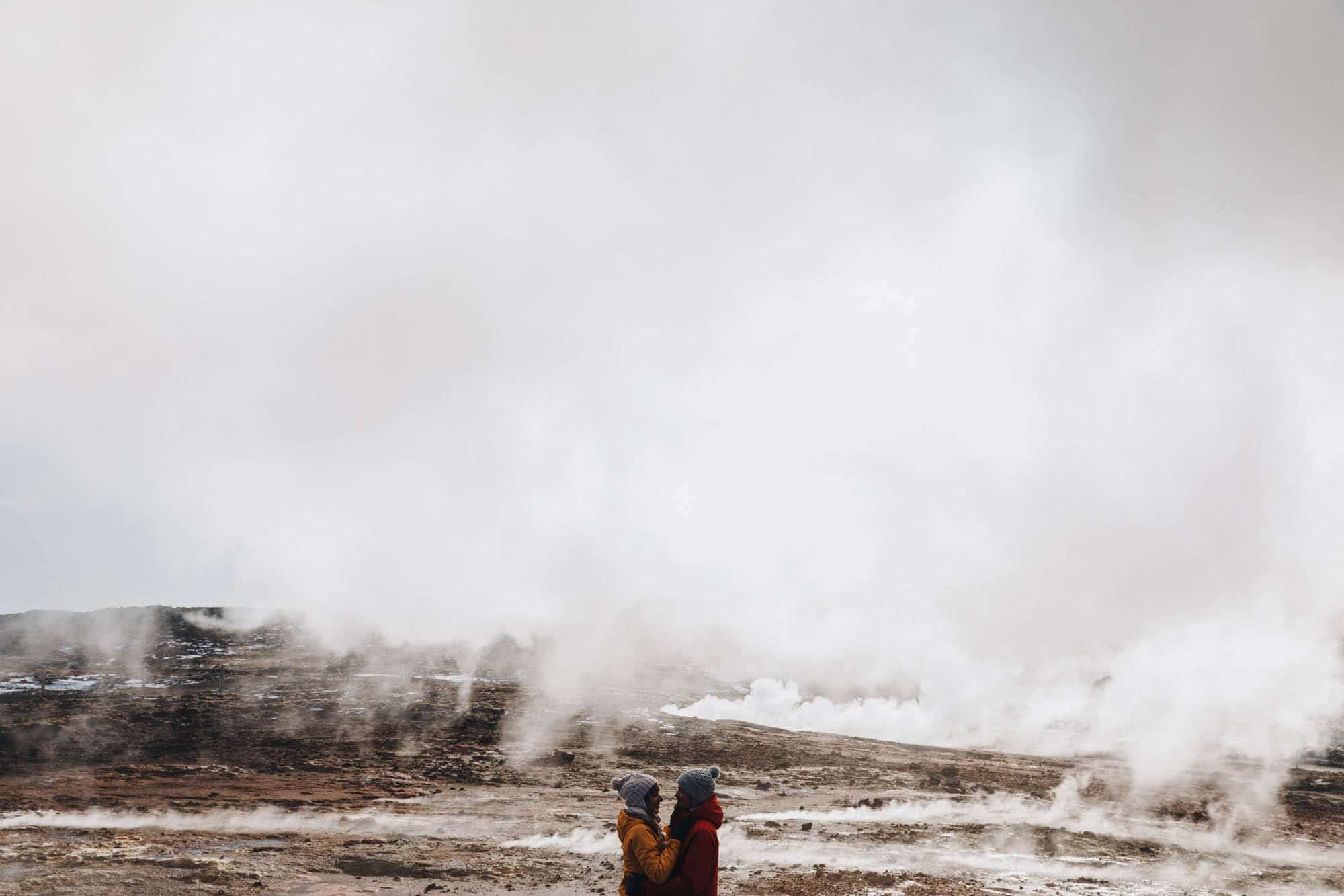 Couple hugging in front of Gunnuhver Geothermal Area in Iceland in winter
