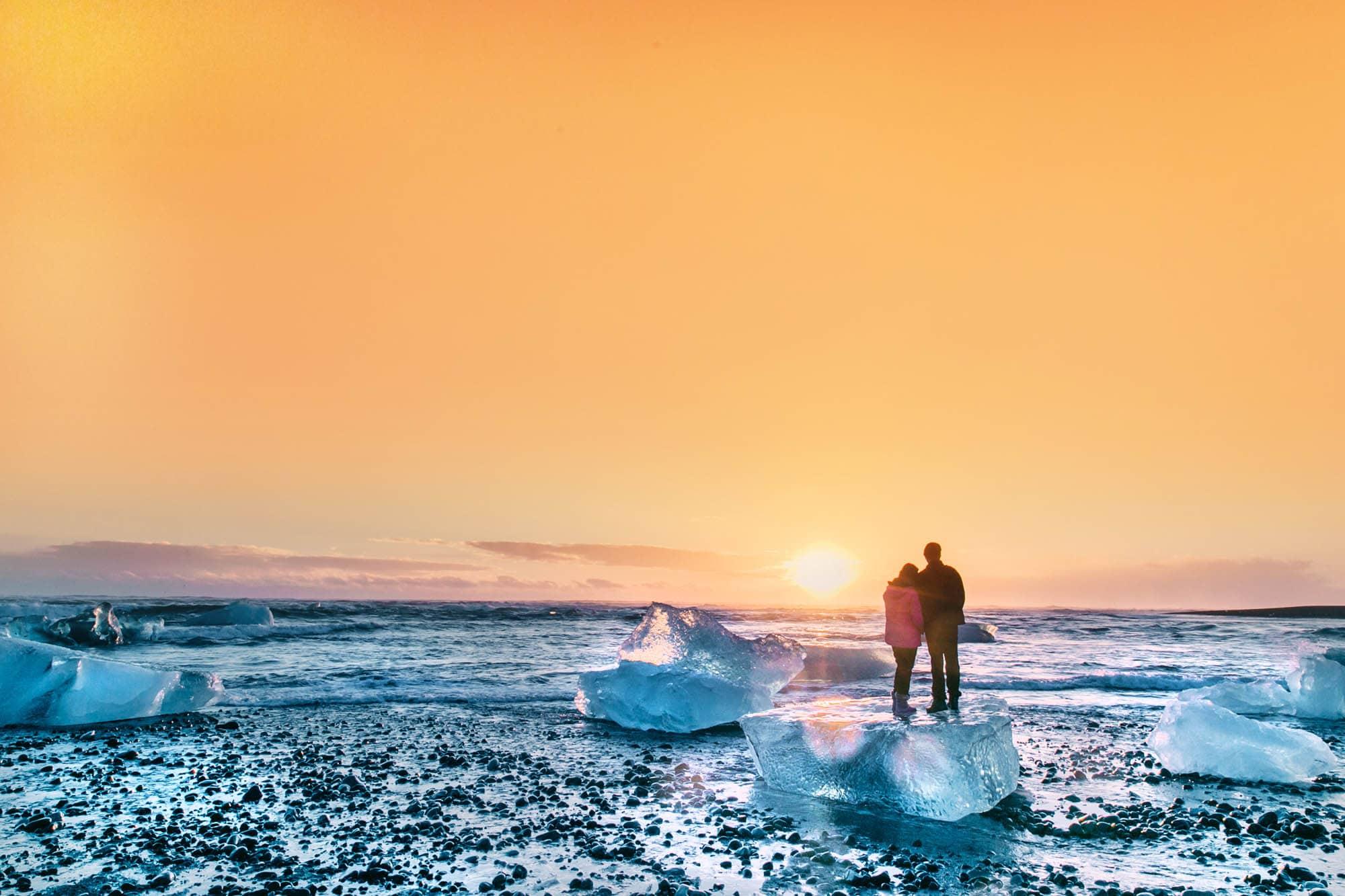 Couple standing and hugging at Jökulsárlón Glacier Lagoon at sunset - honeymoon iceland