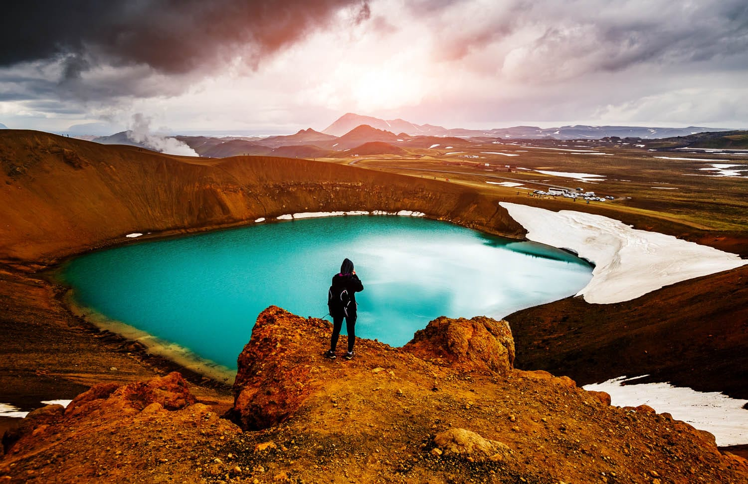 Person standing over Krafla looking into distance, blue water