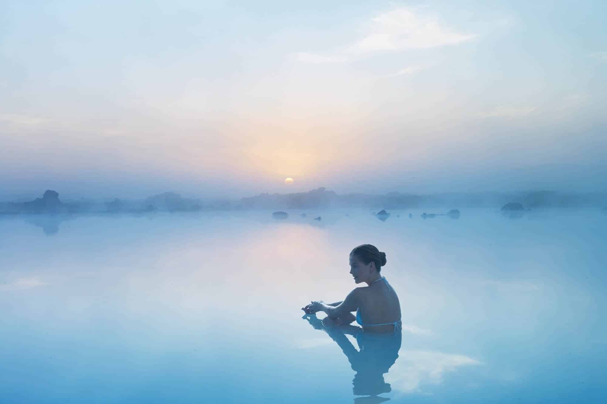 Woman sitting in Blue lagoon at sunset
