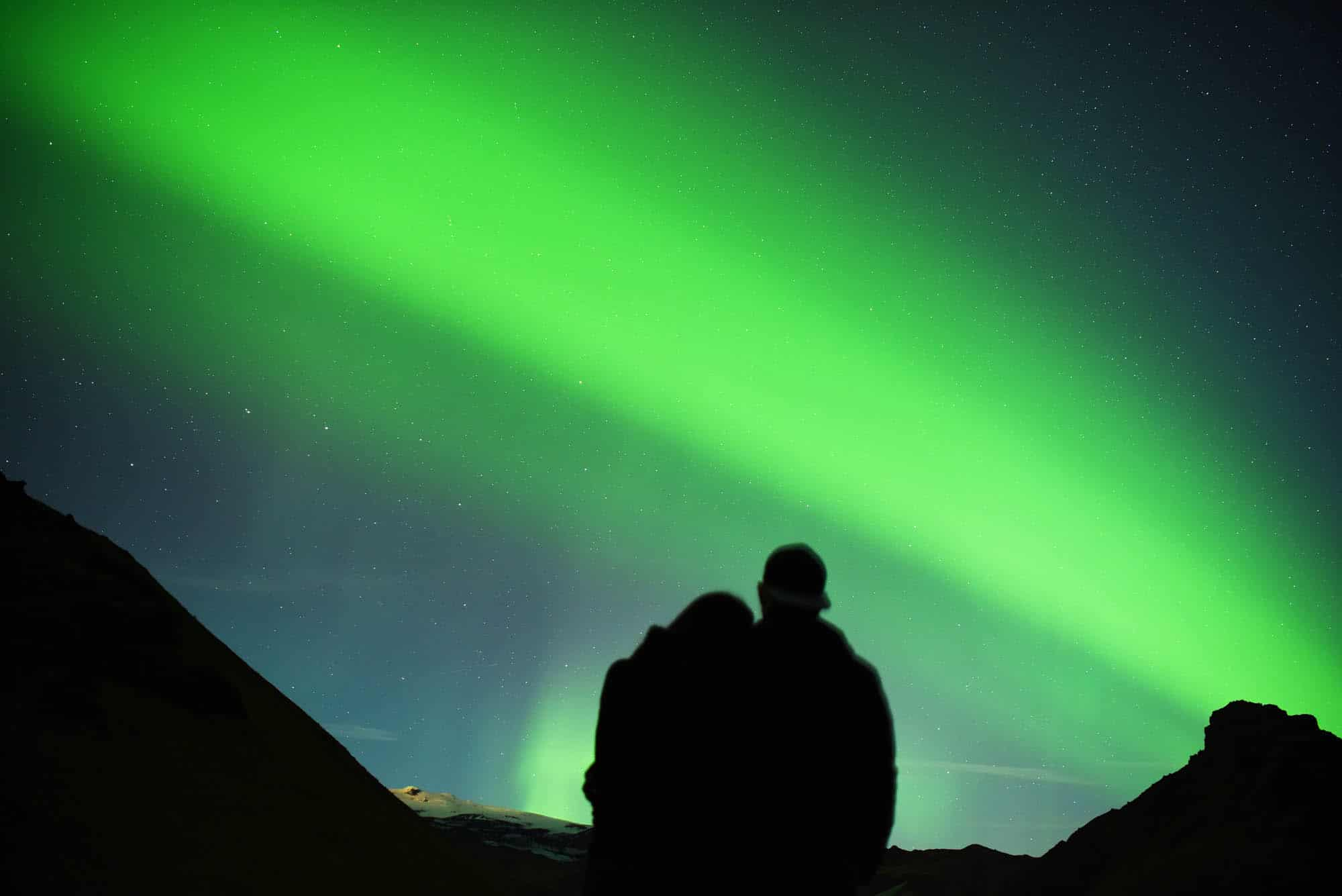 Couple hugging and watching northern lights in Iceland