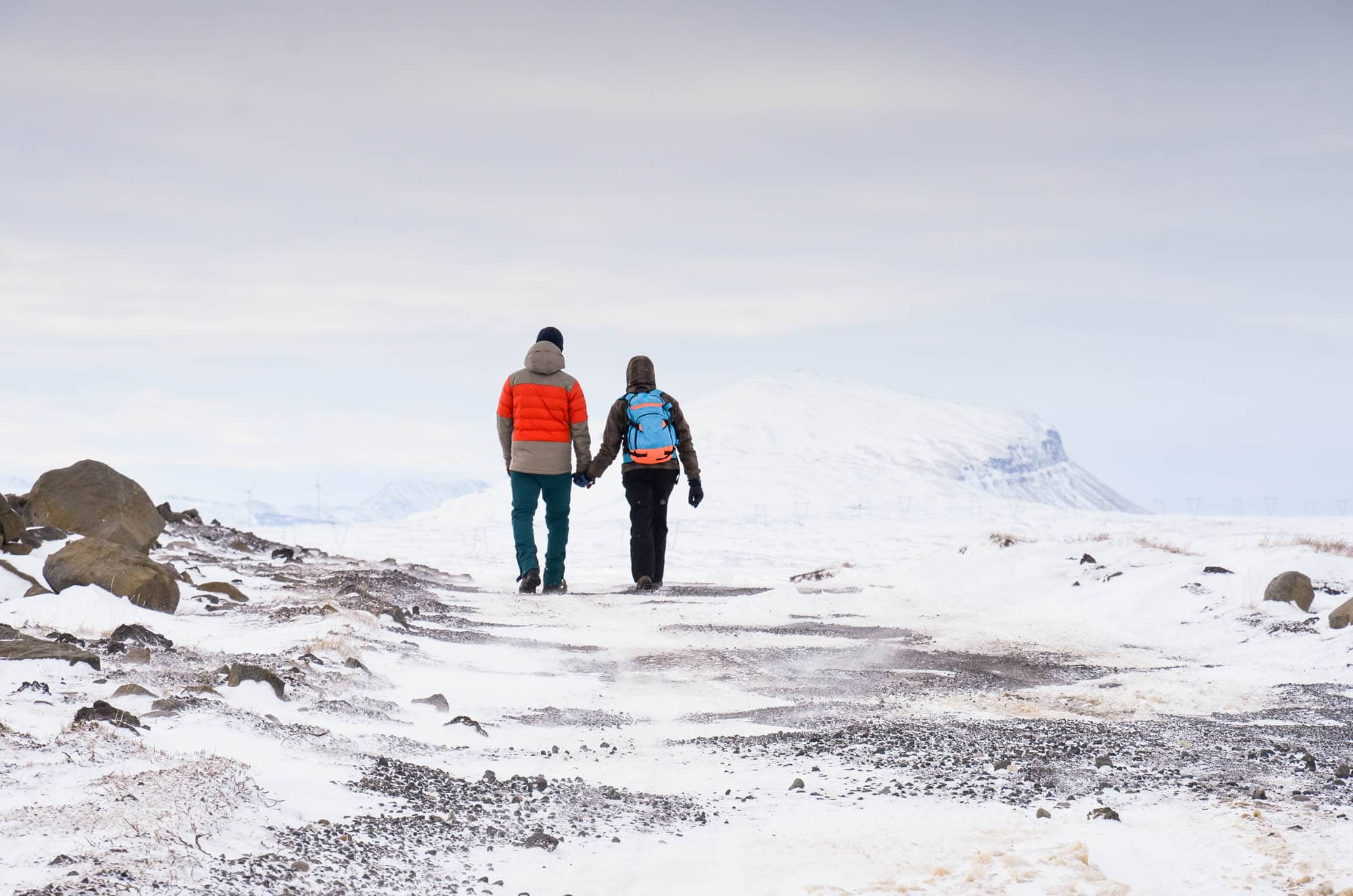 Couple holding hands and waking in Iceland during winter