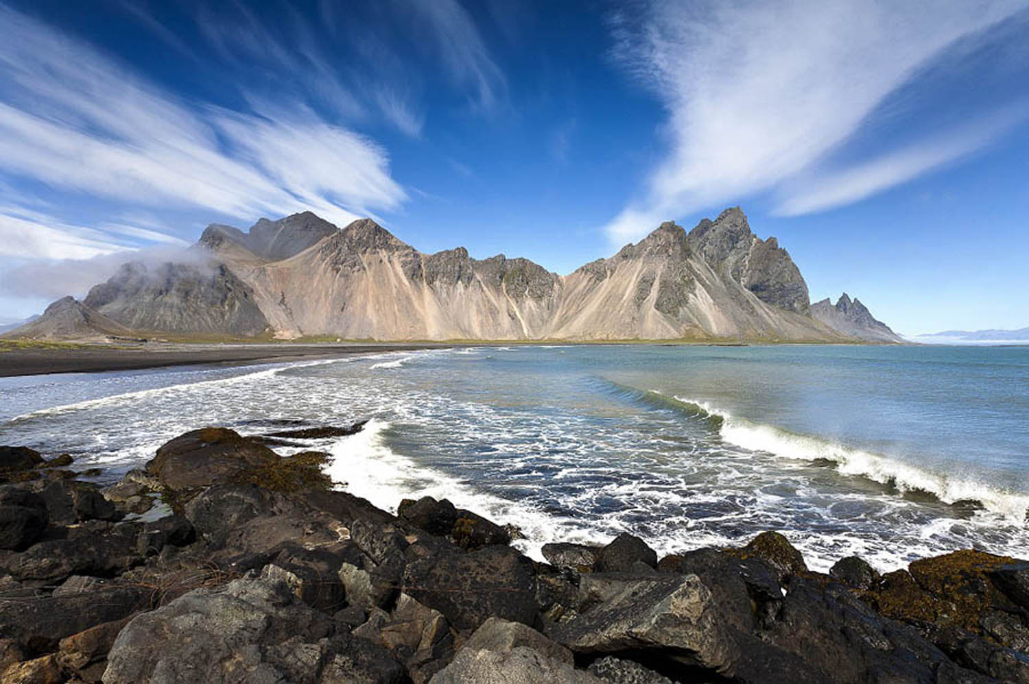 Stokksnes with clear blue sky and few white clouds