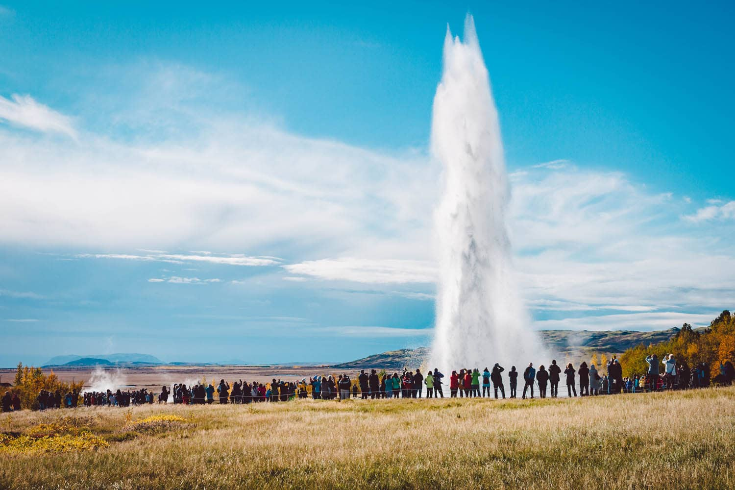 Erupting Strokkur with people watching it