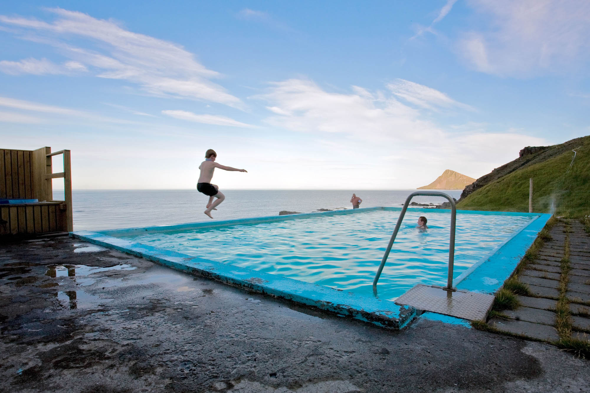 Person jumping into Krossneslaug pool in Strandir- Iceland Westfjords Tour