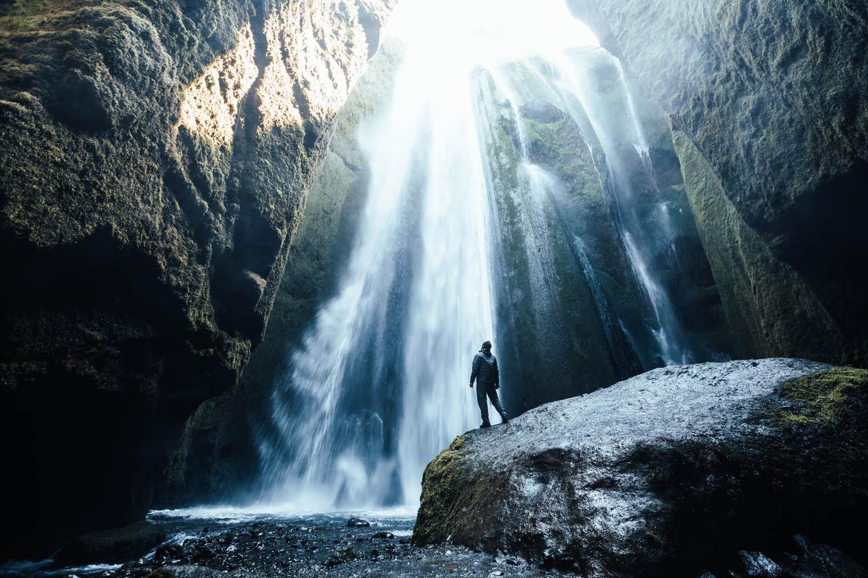 Person standing inside of waterfall - Gljúfrabúi - hidden waterfall Iceland