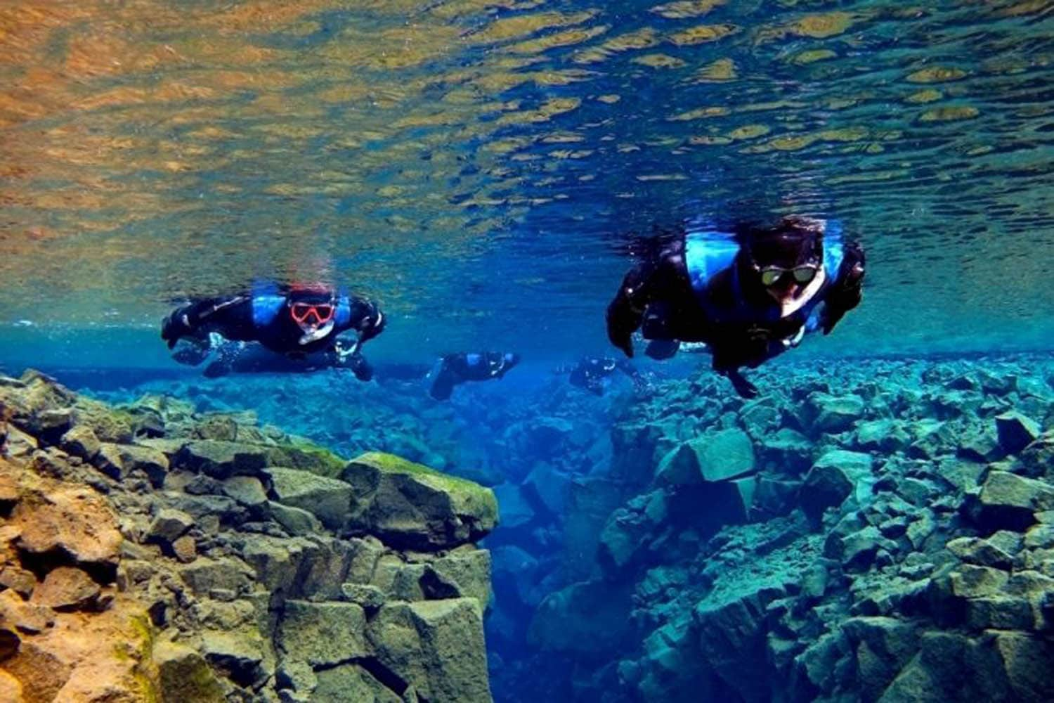 People snorkeling in Silfra, crystal clean water