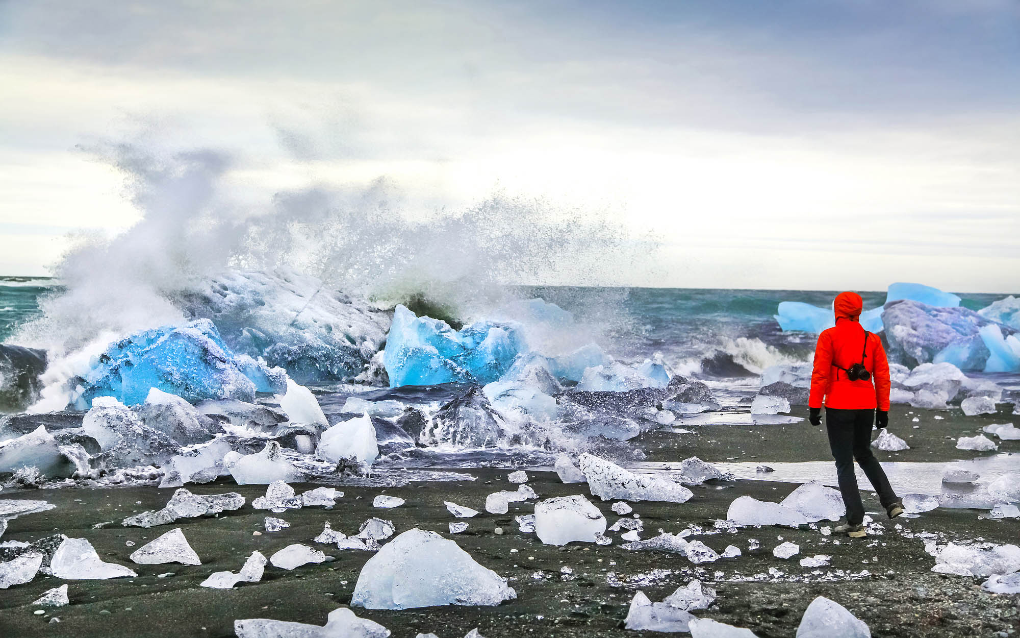 Person in red Jacket looking at Winter Icebergs in Jökulsarlon Glacier Lagoon